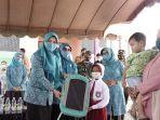 penjabat-ketua-pkk-pkalsel-safriati-safrizal-za-serahkan-tas-kepada-seorang-anak-08062021.jpg