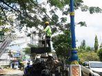 petugas-dinas-permukiman-dan-perumahan-kabupaten-banjar-membenahi-lampu-pju-27042021.jpg