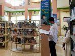 petugas-dinas-perpustakaan-kabupaten-balangan-mengecek-buku-tamu-di-perpustakaan.jpg