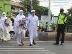 petugas-membantu-menyebrangkan-jemaah-di-jalan-raya-agar-terhidar-dari-kecelakaa.jpg