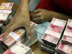 petugas-menghitung-uang-rupiah-di-jasa-penukaran-uang-di-jakarta-pusat_20150724_170739.jpg