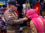 petugas-satpol-pp-memasangkan-masker-kepada-seorang-lansia-di-pasar-nagara-kabupaten-hss.jpg