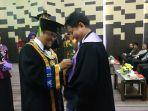 rektor-ulm-prof-sutarto-hadi-memakaikan-toga-ke-guru-besar-prof-dr-drg-rosihan-adhani.jpg