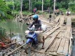 warga-desa-kambiyain-melewati-jembatan-darurat-sementara-pasca-putusnya-jembatan-gantung.jpg