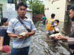 warga-di-tengah-banjir-menerima-makanan-yang-dibagikan-anggota-sabhara-polresta-banjarmasin.jpg