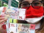 warga-memperlihatkan-uang-kertas-baru-pecahan-rp-75000-usai-proses-penukaran.jpg