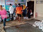 warga-mengambil-paket-bantuan-berupa-ikan-segar-di-kantor-desa-tanjung-rema-kota-martapura.jpg