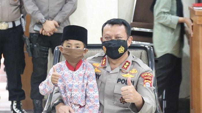 Kapolda Banten Irjen Pol Rudy Heriyanto memangku adik Ade Kosasih (19) di Mapolda Banten, Kota Serang, pada Senin, (24/05/2021). Ade Kosasih merupakan remaja asal Cibaliung Pandeglang yang bekerja menjadi tukang ojek dan pencabut bulu ayam demi menghidupi ima adiknya yang yatim.