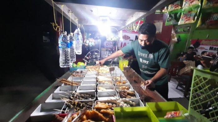 Ismail Saleh (34), pemilik Angkringan 'Mas Coy' tampak sedang sibuk melayani pesanan para pelanggannya.