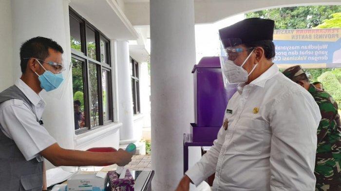 Gubernur Banten Wahidin Halim mengecek suhu tubuhnya sebelum membuka resmi vaksinasi perdana di Pendopo Bupati Tangerang, Kamis (14/1/2021).