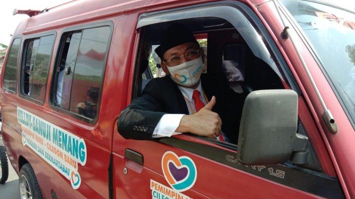 Calon Wali Kota dan Wakil Wali Kota Cilegon yang diusung Partai Berkarya dan PKS, Helldy Agustian-Sanuji Pentamarta, mengendarai angkot saat mendaftar ke kantor KPU Kota Cilegon, Sabtu (5/9/2020).