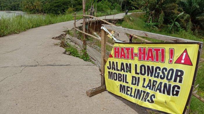 Pengendara sepeda motor secara perlahan melintasi jalan provinsi penghubung Kecamatan Cikeusik dan Kecamatan Cibaliung Kabupaten Pandeglangyang sudah rusak berat pada Selasa (23/2021). Jalan itu mengalami longsor karena hujan lebat beberapa waktu lalu.