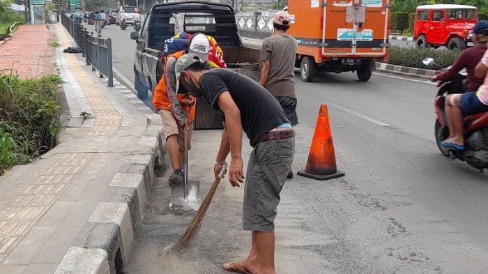 Petugas Dinas PU membersihkan serpihan dari aspal yang rontok di Jalan Ciater Raya Serpong, Tangerang Selatan pada Jumat (11/12/2020).