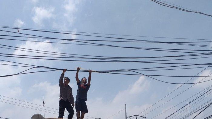 Ganggu Kendaraan, Kabel Terjuntai di Jalan Raya Serang Dirapihkan Petugas Polsek Kramatwatu