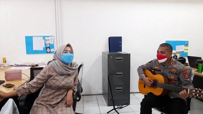 Kabid Humas Polda Banten AKBP Shinto Silitonga bermain gitar di ruang redaksi TribunBanten.com di sela kunjungannya, Senin (23/8/2021).