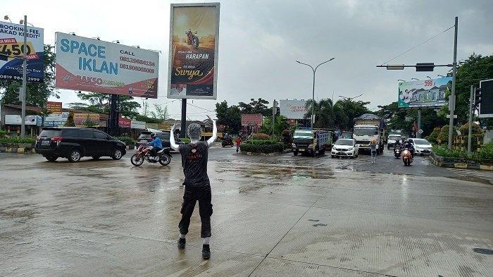 Manusia silver mengatur lalu lintas kendaraan di persimpangan lampu merah Jalan Lingkar Selatan (JLS) Kota Cilegon, Sabtu (3/4/2021). Lampu merah di persimpangan jalan tersebut mati setelah tersambar petir pada Jumat malam.