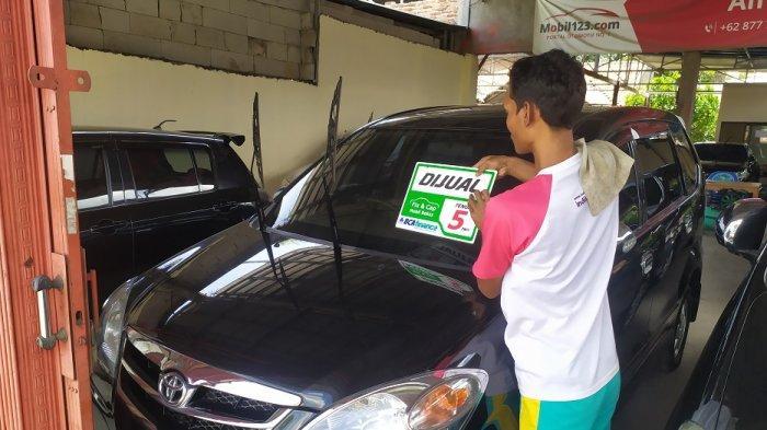 Seorang penjual mengelap mobil bekas yang dijual di sebuah showroom di Letnan Jidun, No 9 Kepandean, Kota Serang, Senin (14/12/2020).