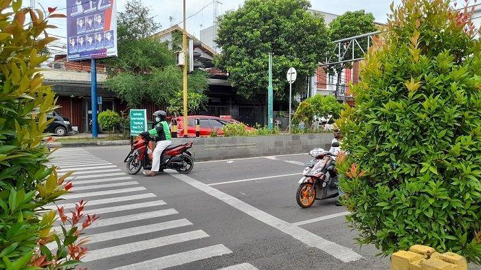 Pengendara sepeda motor ojek online tampak melewati marka pembatas jalan dan hendak putar balik pada hari pertama pemberlakuan Electronic Traffic Law Enforcement (ETLE) atau tilang elektronik di persimpangan lampu merah Pisang Mas, Kota Serang, Banten, Kamis (1/4/2021).