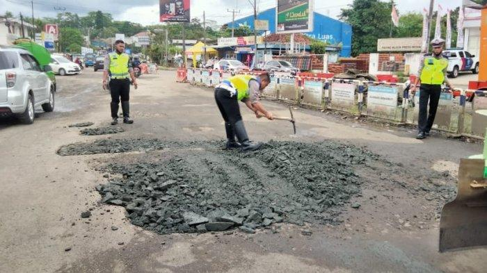 Aparat Polres Lebak bersama elemen masyarakat memperbaiki jalan di Bundaran Mandala, Kadu Agung, Cibadak, Kabupaten Lebak, Banten.