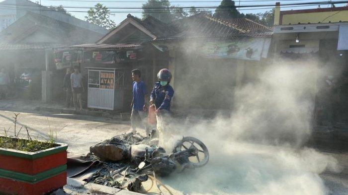 Petugas Damkar Lebak saat memadamkan api sepeda motor yang terbakar di Jalan Raya Cipanas, Rangkasbitung, Kabupaten Lebak, Selasa (27/7/2021).