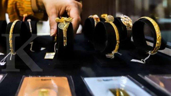 ILUSTRASI. Petugas menunjukkan produk perhiasan emas dan emas batangan di gerai Galeri 24 Pegadaian, Jakarta, Selasa (21/4/2020).