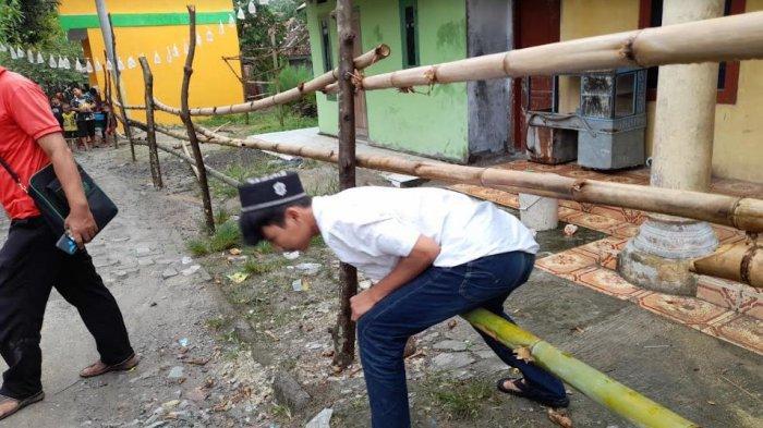 Penghuni rumah di Kampung Kabayan, Desa Bandung, Kecamatan Bandung, Kabupaten Serang kesulitan untuk keluar masuk rumah karena dipasangi pagar bambu oleh saudaranya sendiri