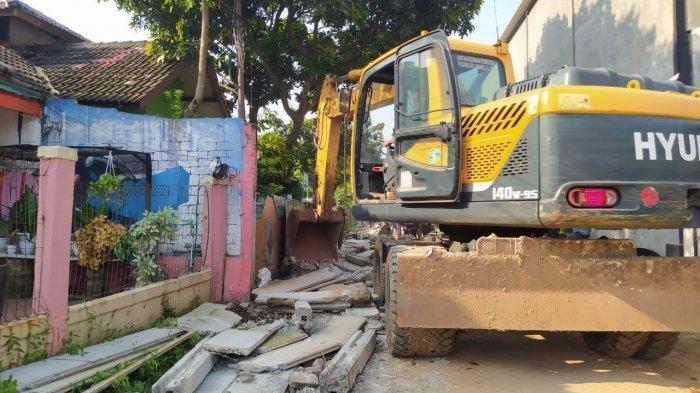 Satpol PP Kota Tangerang dengan ekskavator merobohkan pagar tembok beton sepanjang 300 meter dan setinggi 2 meter yang mengurung satu rumah di Kecamatan Ciledug, Kota Tangerang, pada Rabu (17/3/2021).