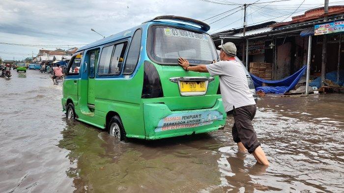 Sopir angkot mendorong mobilnya yang mogok di akses jalan menuju Pasar Induk Rau di jalan Jamaksari, Kelurahan Cimuncang, Selasa (14/9/2021).