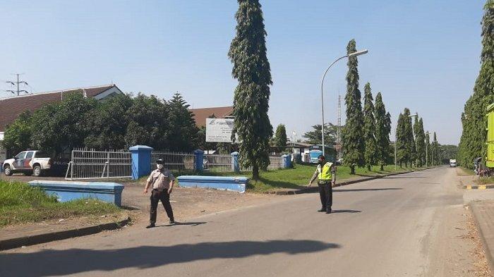 Petugas menunjukkan lokasi tabrakan dua sepeda motor di Jalan Australia II Kawasan Industri Krakatau Steel, Kecamatan Ciwandan, Kota Cilegon, Selasa (27/7/2021). Kecelakaan itu mengakibatkan seorang pengendara tewas.