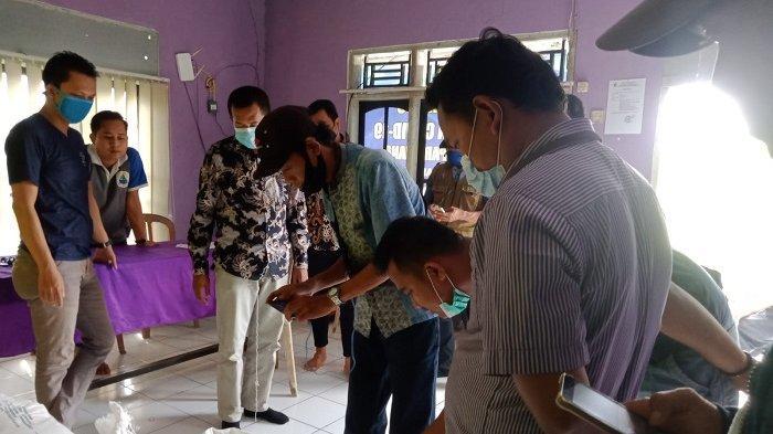 Pihak Bulog memeriksa kondisi beras bantuan sosial PPKM Darurat di Desa Parahiang, Kecamatan Leuwidamar, Kabupaten Lebak, Banten. Warga menerima beras tersebut dalam kondisi busuk.