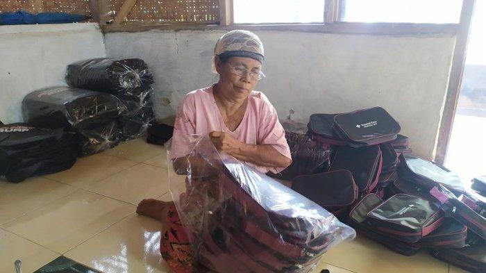 Warga memasukkan tas ke dalam wadah di Desa Kadu Genep, Kecamatan Petir, Kabupaten Serang, Sabtu (19/12/2020).
