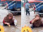 ibu-ibu-makan-biskuit-sambil-celupin-ke-air-banjir.jpg