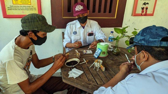 Nur Kholis (kiri) mempraktikkan cara ngelelet rokok di depan anggota DPD ASITA DIY, Jumat (4/6/2021).