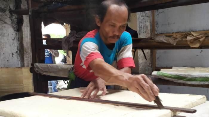 Teguh Setianto, pengrajin tahu di Kaliputih, Kelurahan Purwokerto Wetan, Purwokerto Timur, sedang memotong tahu yang akan dijual, Senin (4/1/2020).