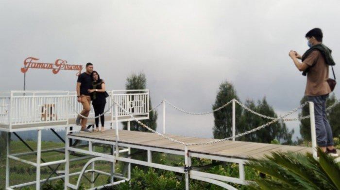 Pengunjung foto di spot foto yang disediakan pengelola tempat wisata Posong di lembah Gunung Sindoro, Kabupaten Temanggung, Minggu (11/10/2020).