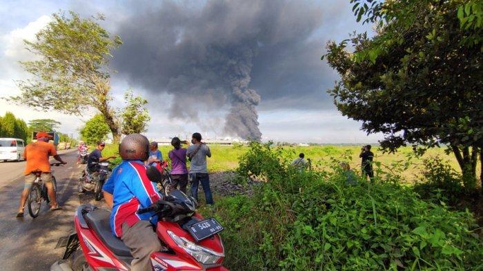 Warga sekitar melihat kepulan asap hitam, paska kebakaran yang terjadi salah satu tanki yang berisi benzene Pertamina RU IV Kabupaten Cilacap, Sabtu (12/6/2021).