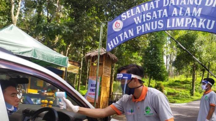 Petugas mengecek suhu tubuh pengunjung tempat wisata Hutan Pinus Limpakuwus, Banyumas, Sabtu (6/12/2020).