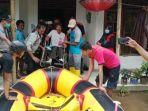 anggota-bpbd-banyumas-mengevakuasi-warga-terdampak-banjir-di-desa-sidamulya-banyumas.jpg