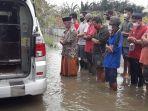 foto-keluarga-dan-petugas-melakukan-salat-jenazah-di-tengah-banjir-saat-pemakaman-pasien-covid.jpg