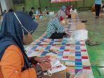 pekerja-melipat-surat-suara-untuk-pilkada-pekalongan-di-lapangan-futsal-karangsari.jpg