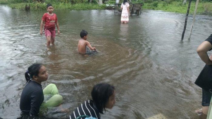Air pasang di Kampung Suak Rasau, Desa Sungai Buluh, Kecamatan Singkep Barat, Kabupaten Lingga, Jumat (1/1/2021). Beberapa anak terlihat bermain di air pasang