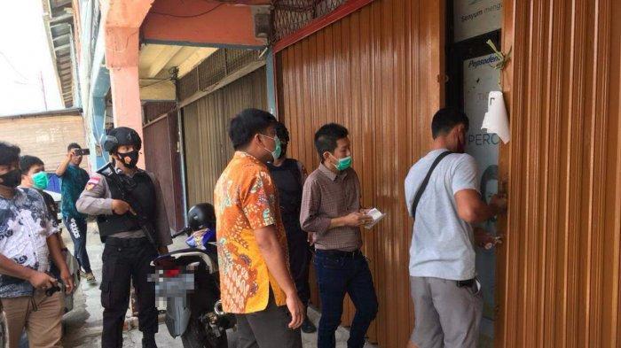 Tim KPK dan beberapa pria saat hendak masuk ke gudang lain dekat gudang CV Three Star Bintan, Rabu (3/3/2021)