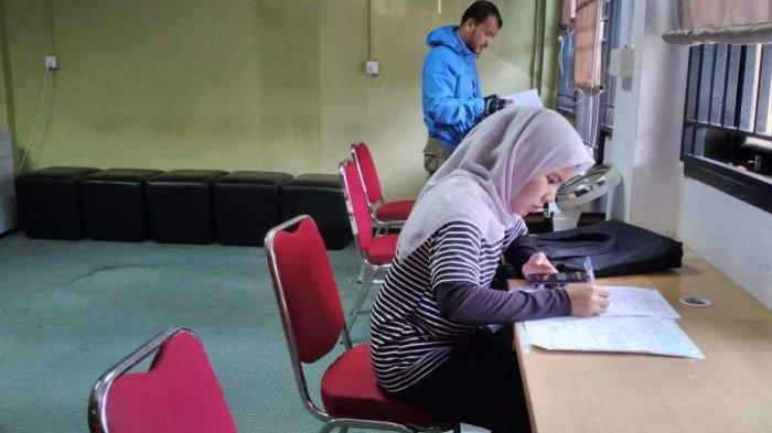 Seorang pencari kerja sedang mengisi formulir persyaratan kartu kuning