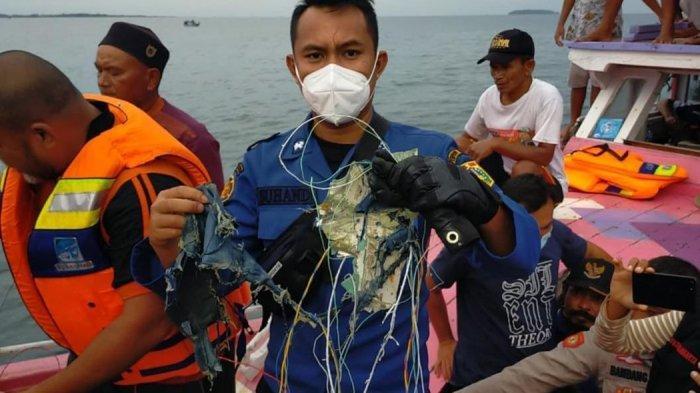 Petugas menunjukkan serpihan barang-barang di lokasi jatuhnya Sriwijaya Air