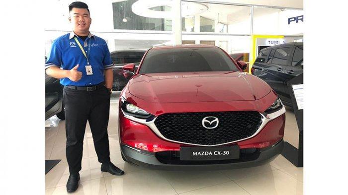 Seorang Mazda Expert tengah berfoto dengan salah satu unit mobil terbaru yakni Mazda CX-30 (9/9/2020) di Showroom Mazda di Jalan Yos Sudarso