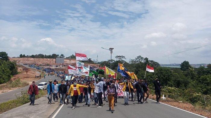 JALAN KAKI - Massa aksi dari mahasiswa berjalan kaki menuju kantor DPRD Kepri di Tanjungpinang, Selasa (13/10/2020) untuk menyuarakan aspirasi menolak UU Cipta Kerja