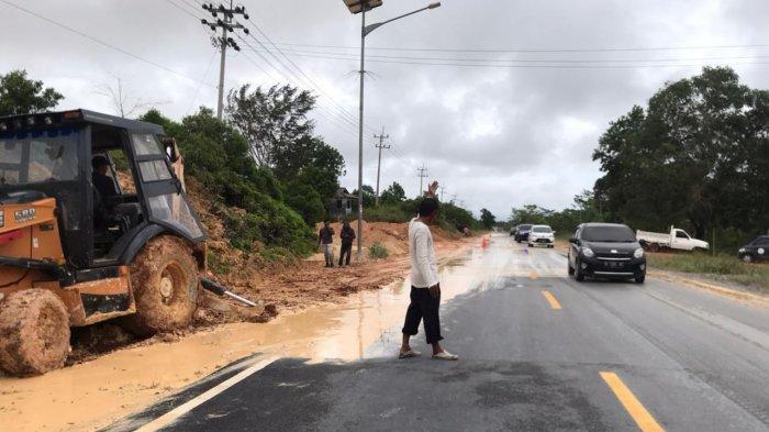 Alat berat diturunkan untuk membersihkan gundukan pasir dan becek di Jalan Lintas Barat Tepat di depan Jalan Kampung Sei Lepan yang becek dan ditutupi gundukan pasir, Selasa (18/5/2021)