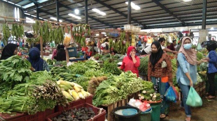 Rika, pedagang sayur di Pasar Bintan Centre Tanjungpinang saat melayani pengunjung yang hendak membeli dagangannya, Selasa, (19/1/2021)