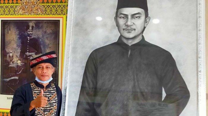 LUKISAN NONG ISA - Pelukis asal Batam, Marani (58), berfoto dengan lukisan buah karyanya yang menggambarkan sosok Raja Isa bin Raja Ali alias Nong Isa di usia muda. Lukisan ini resmi dipajang di Museum Batam Raja Ali Haji, Batam Center, pada Jumat (18/12/2020).
