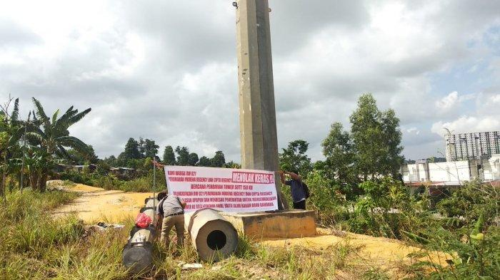 Warga Perumahan Modena, Kelurahan Belian, Kecamatan Batam Kota memasang spanduk menolak pembangunan Tower SUTT 150 yang berada di depan perumahan mereka, Kamis (23/1).
